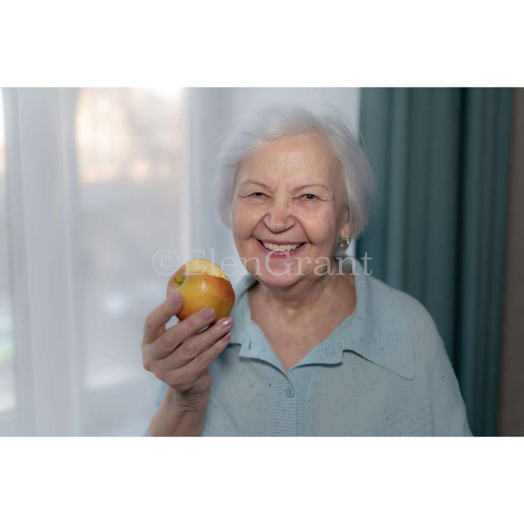 Senior  woman holds an apple and laughs