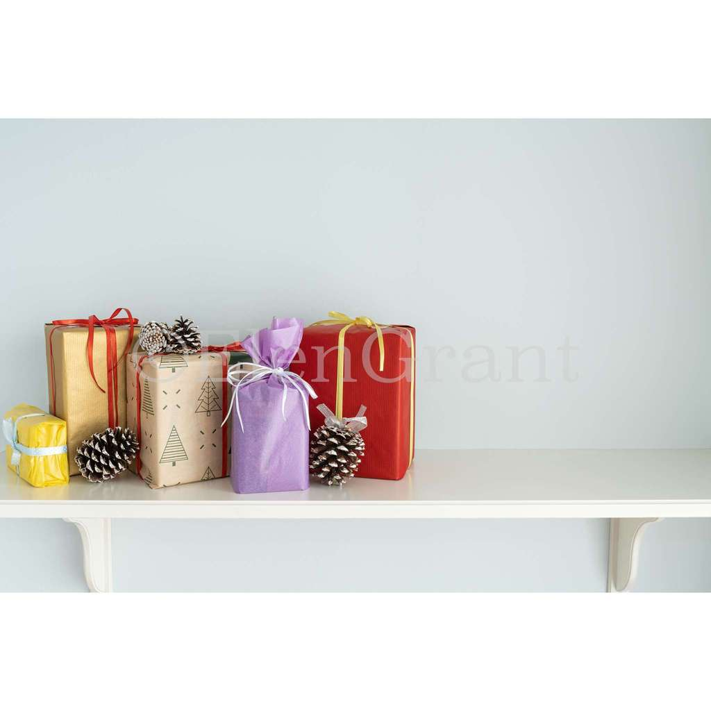 Christmas present boxes with pine cones on the white shelf