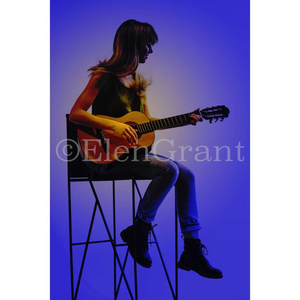 Young woman playing guitar. Blue background